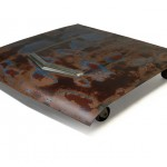 Three quarter view of an industrial table made with the hood of a Ford Falcon 1962 car.