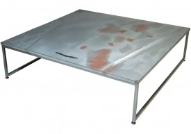 Three quarter view of an industrial table made with the hood of a Ford Thunderbird 1983 car.