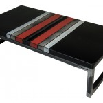 Three quarter view of an industrial table made with the hood of an unknown black, red, grey and white sport car