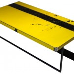 Three quarter view of an industrial table made with the trunk of an unknown yellow and black sport car.