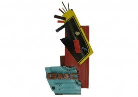 Front view of an artwork made with a 1982 GMC truck emblem and small pieces of steel from old american cars.