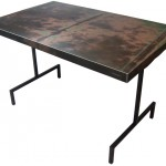Three quarter view of an industrial table made with the hood of a 1979 Ford LTD car.