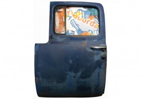 Front view of an artwork made with a 1955 blue Ford truck's door and torn posters.