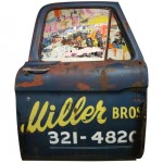 Front view of an artwork made with a 1965 Ford truck's door and torn posters.
